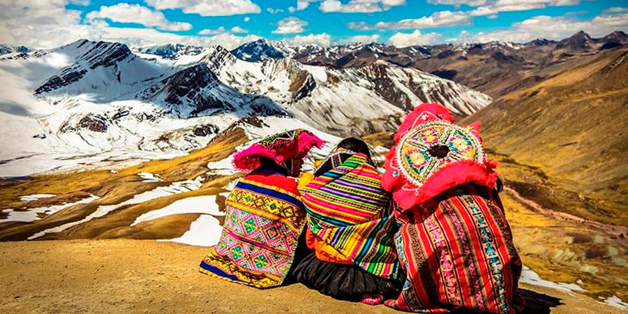 Indigenous Peruvians watching the snowcapped mountain peaks of the Lares Valley in Peru