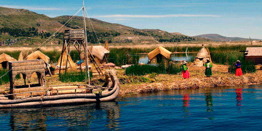A by the indiginous Uru built floating island on the Titicaca lake with the island of Taquile in the background.