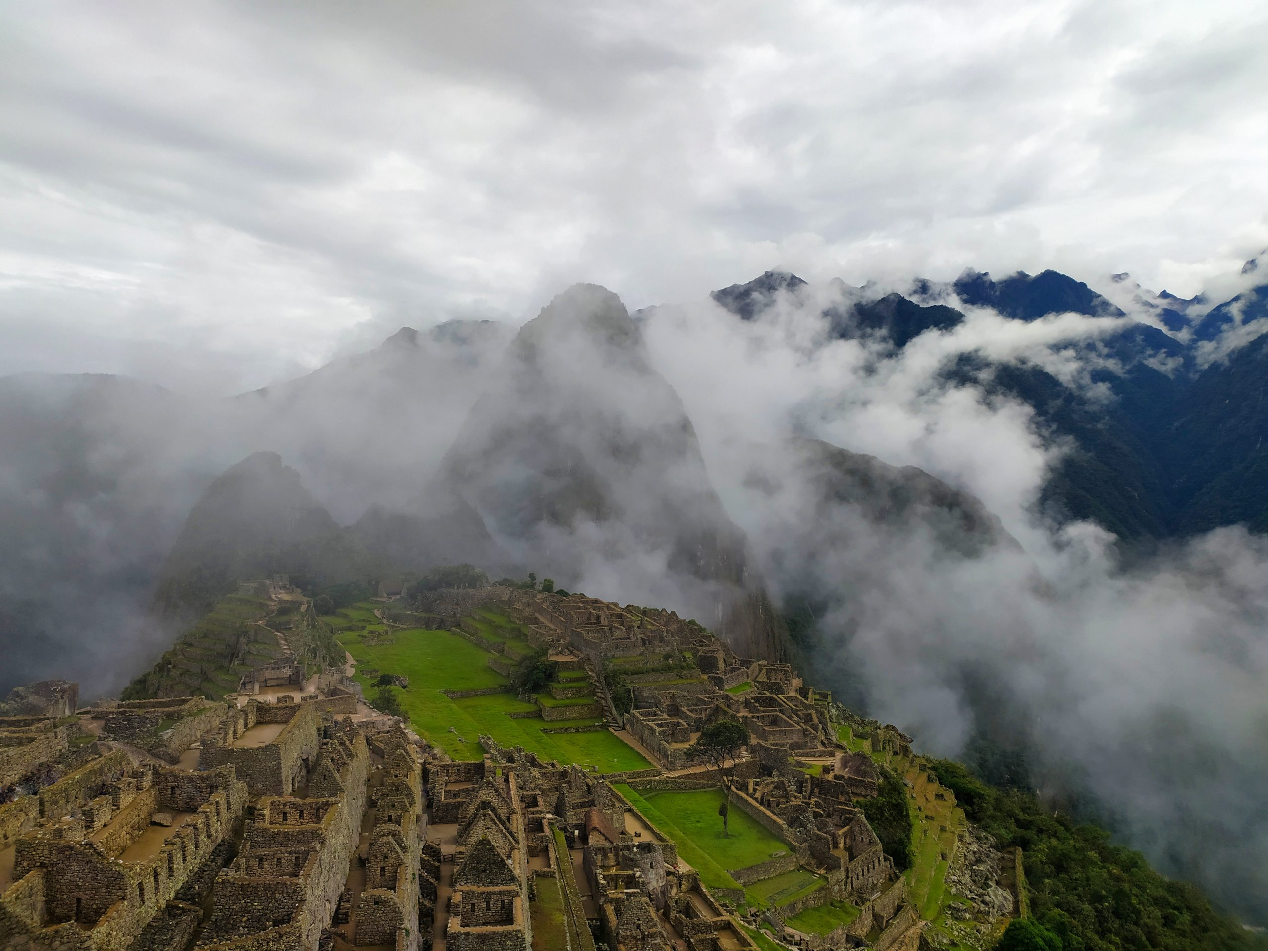The ruins of Machu Picchu coming forth out of the clouds which still partly hide the mountainrange in the background